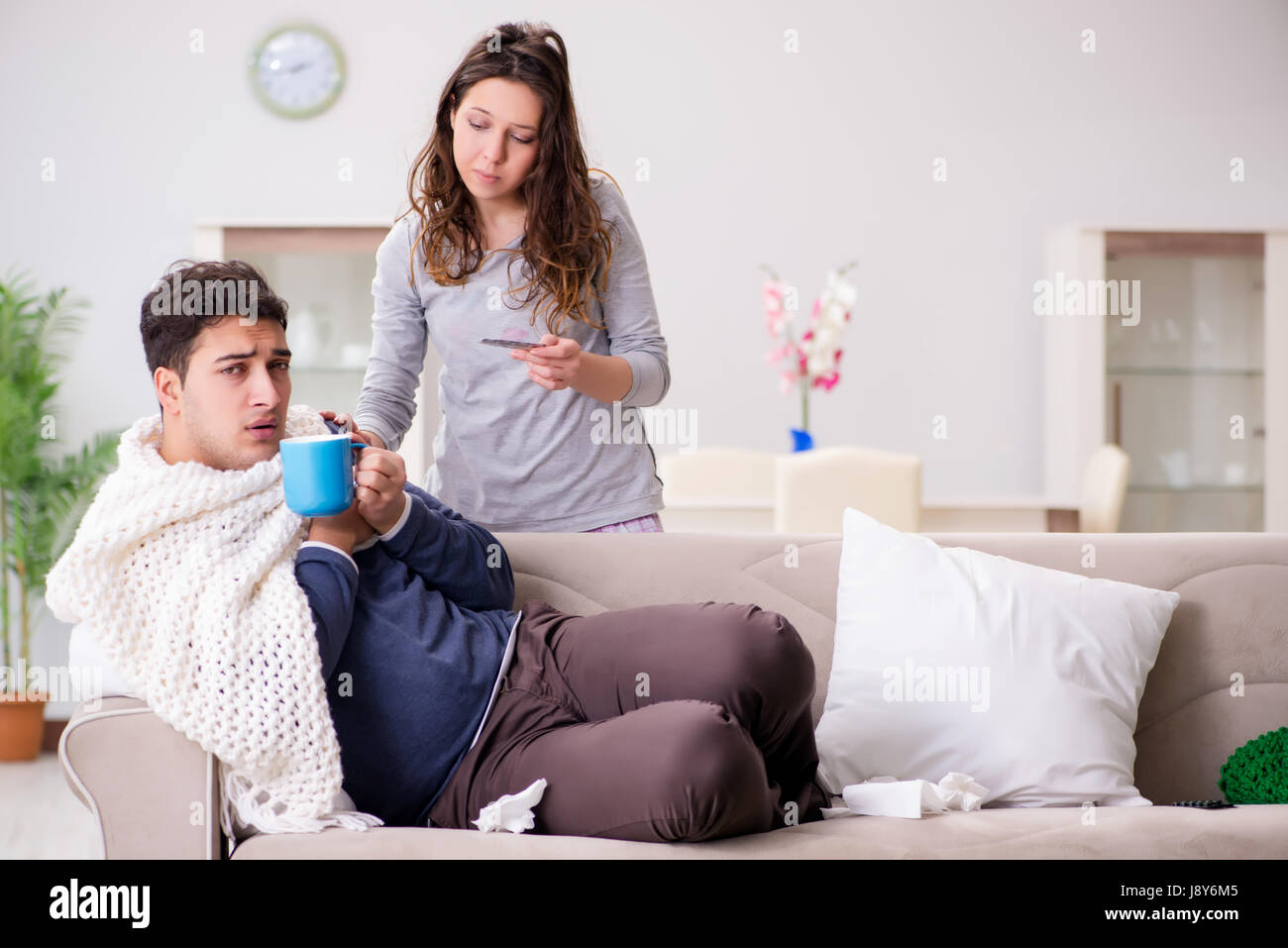 Wife Caring For Sick Husband At Home Stock Photo