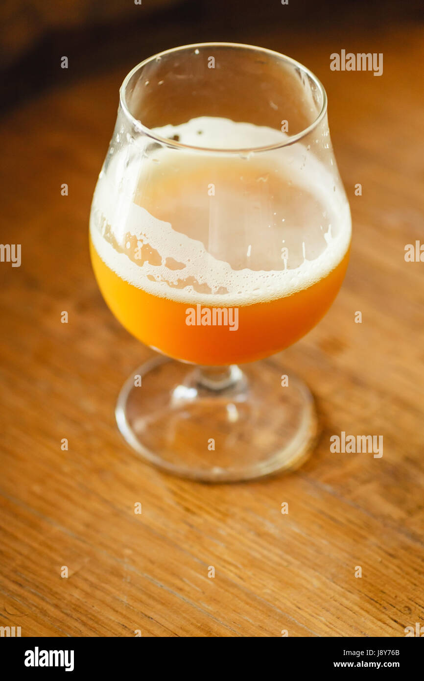 Glass of wheat beer standing on a wooden barrel in a brewery - Stock Image