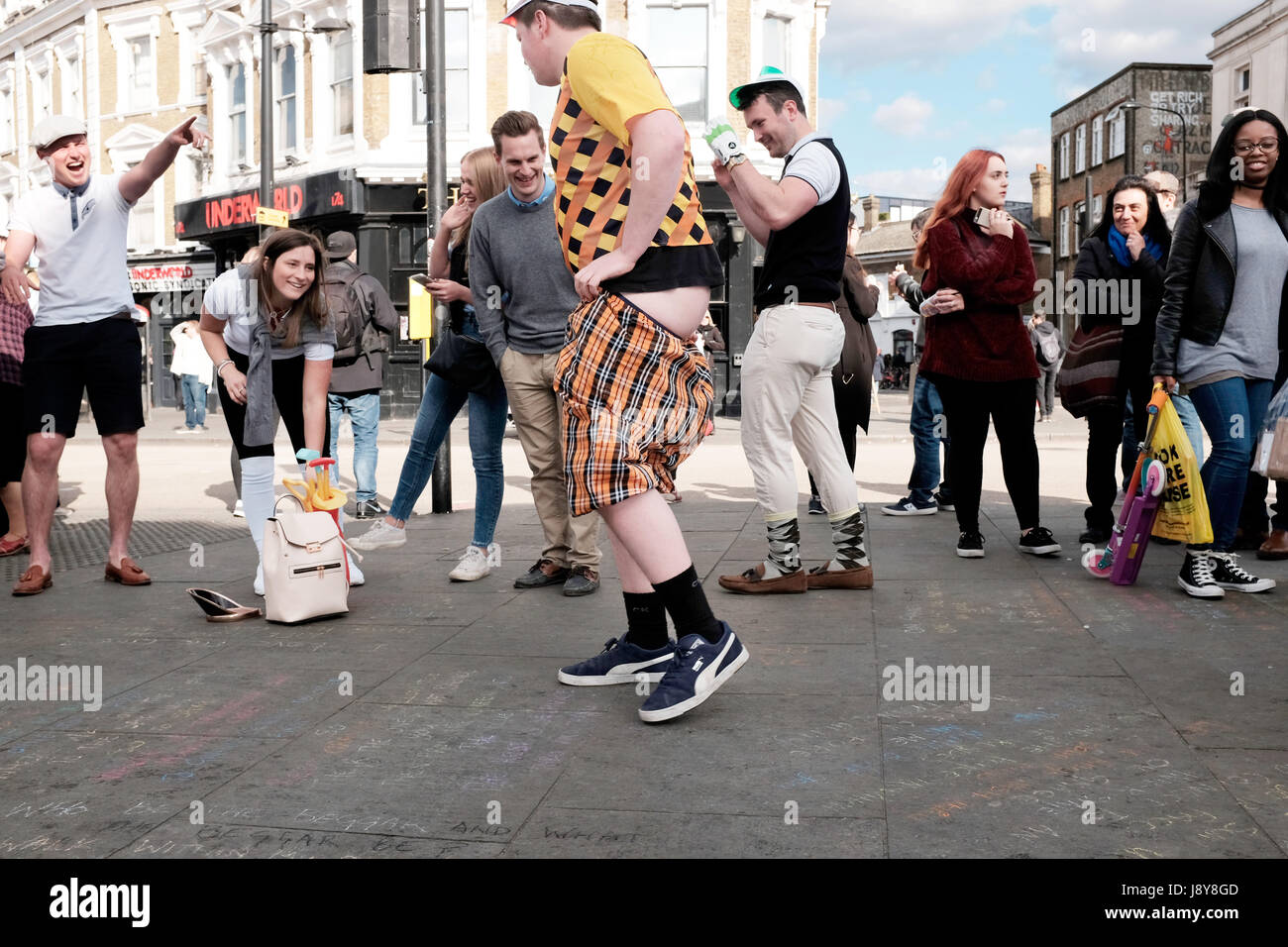 A man pulls down his shorts in Camden Town - Stock Image
