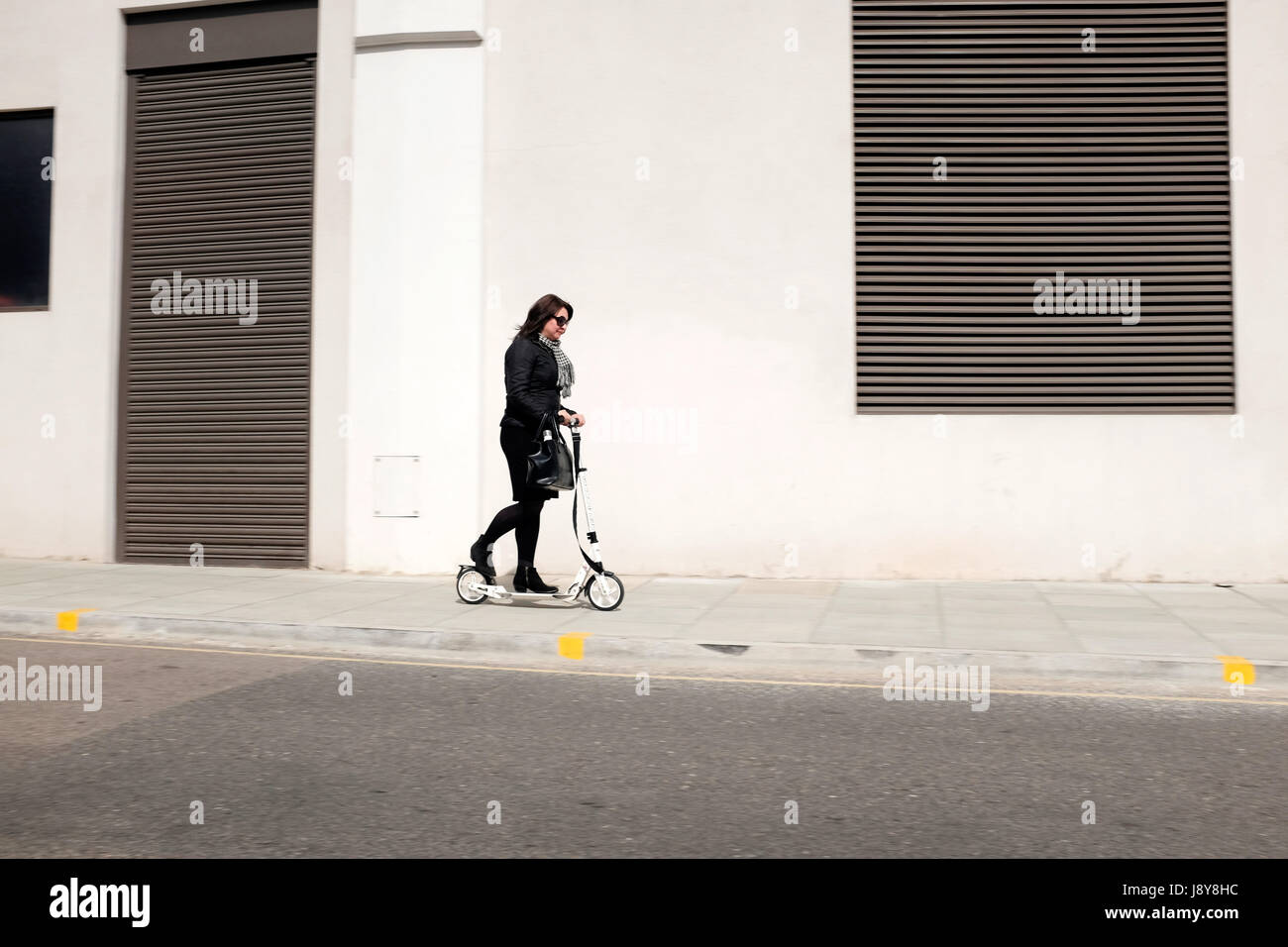 Woman on pedestrian scooter, London, England, UK. - Stock Image