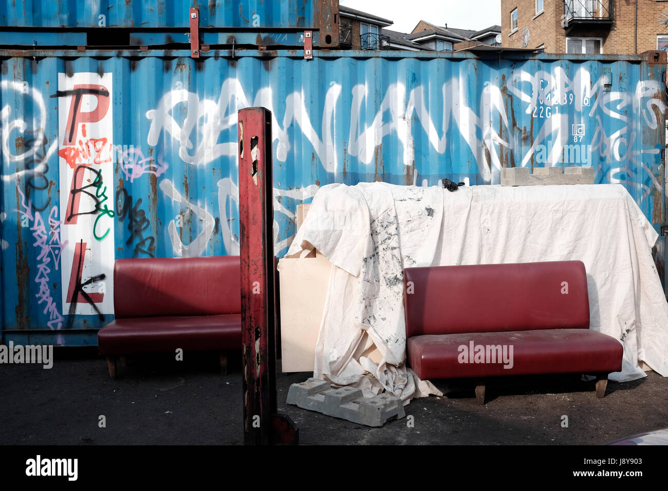 Grafftiti sprayed ship Containers with discarded furniture, on  Westbourne Park road, London, England, UK. - Stock Image