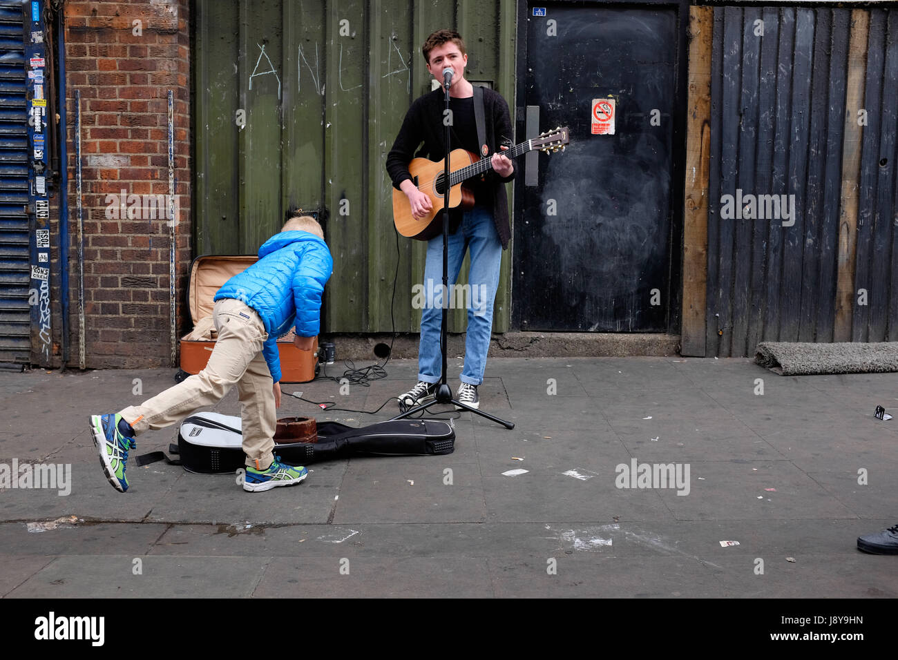 London Street Musician or 'Busker', playing guitar and singing on the streets of Camden Town, London. - Stock Image