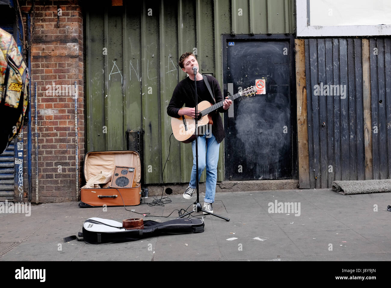 London Street Musician or Busker, playing guitar and singing on the streets of Camden Town, London. - Stock Image