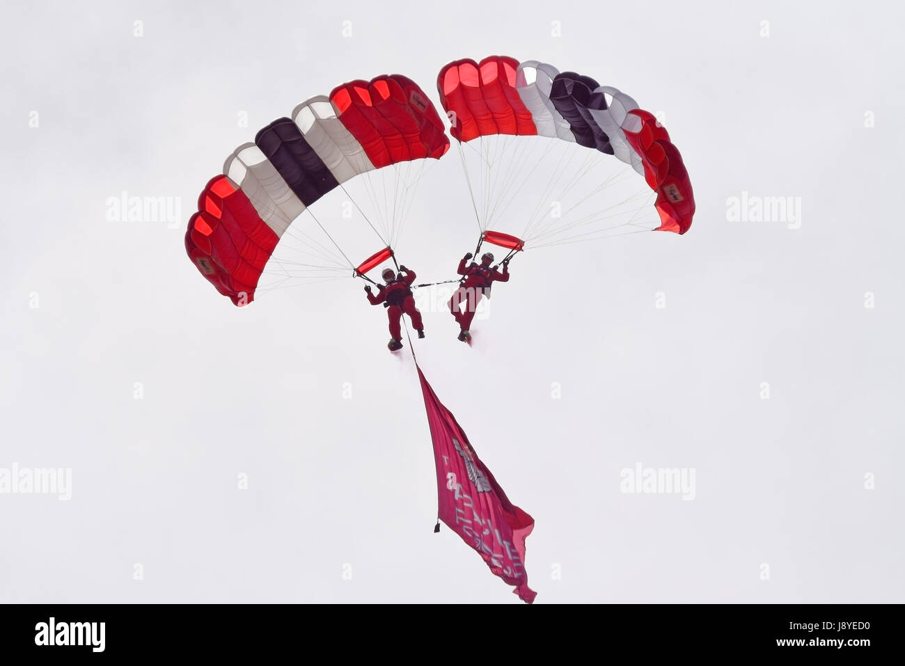 Two of the The Red Devils parachute team joined together with flag. Space for copy - Stock Image