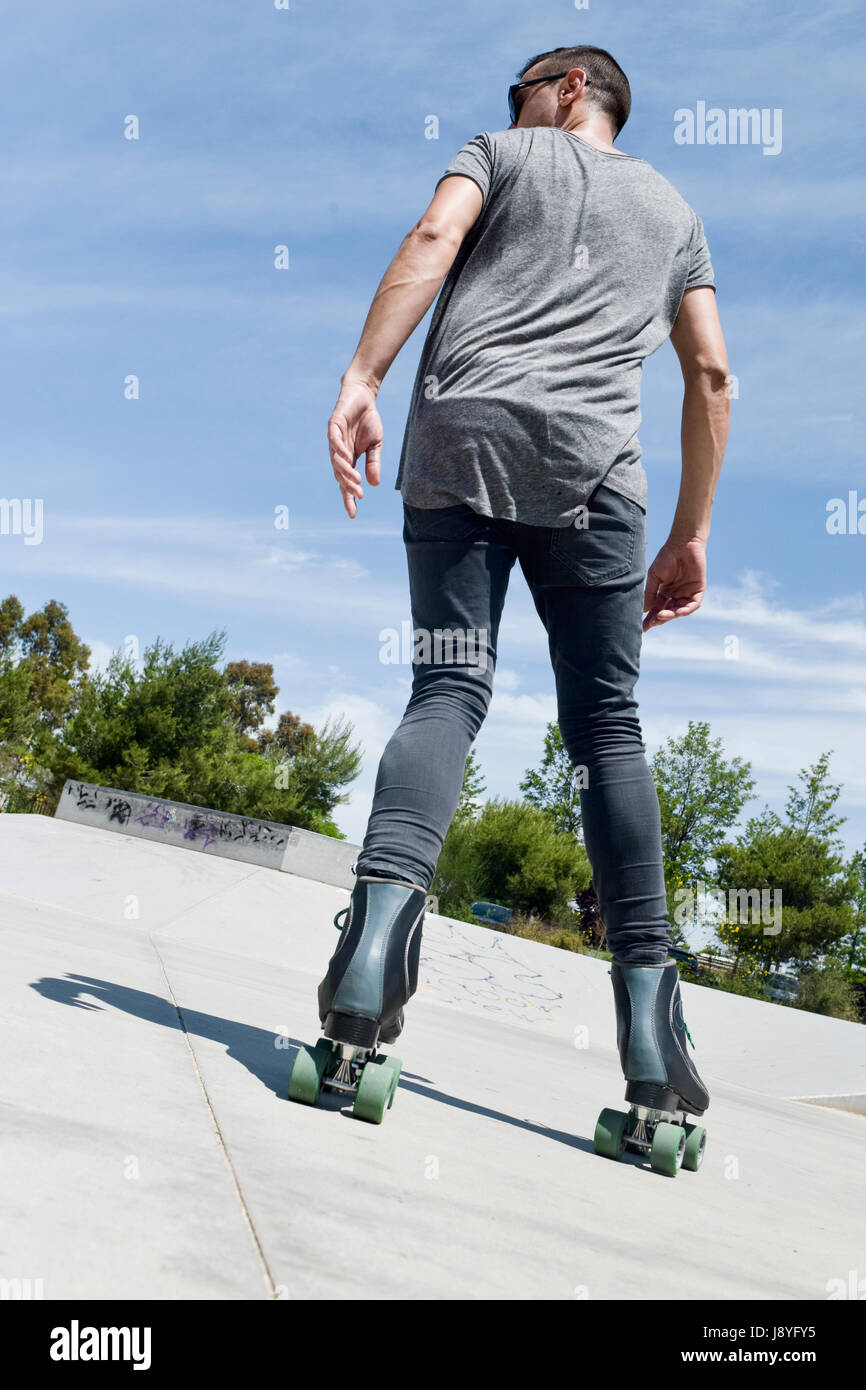 A Young Caucasian Man Roller Skating Backwards With Quad Skates In An  Outdoors Skate Park Stock Photo - Alamy