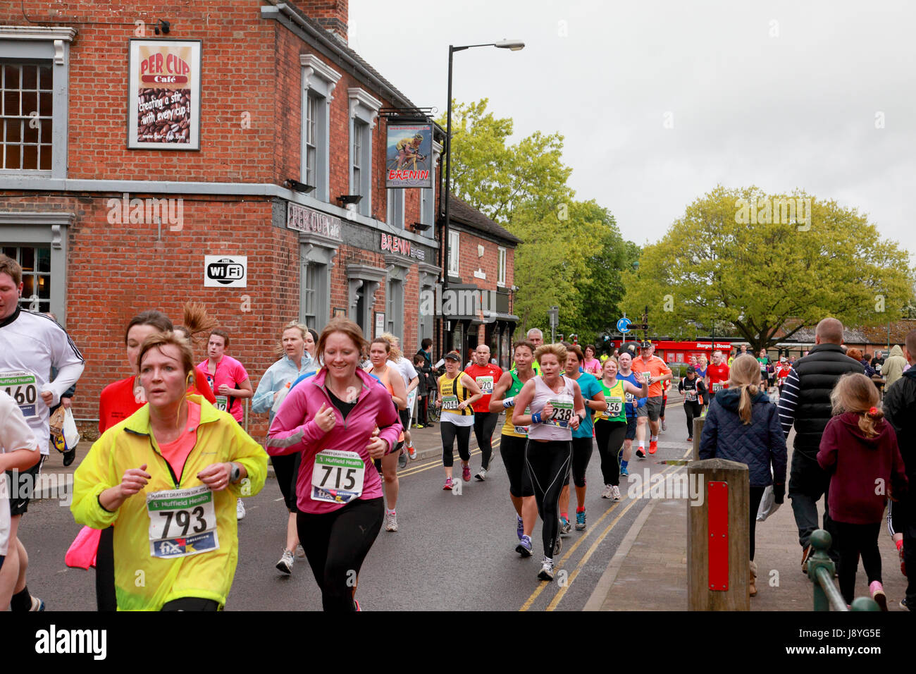 Some of the 2,500 runners in the Market Drayton 10K race running down the main street in the centre of the town - Stock Image