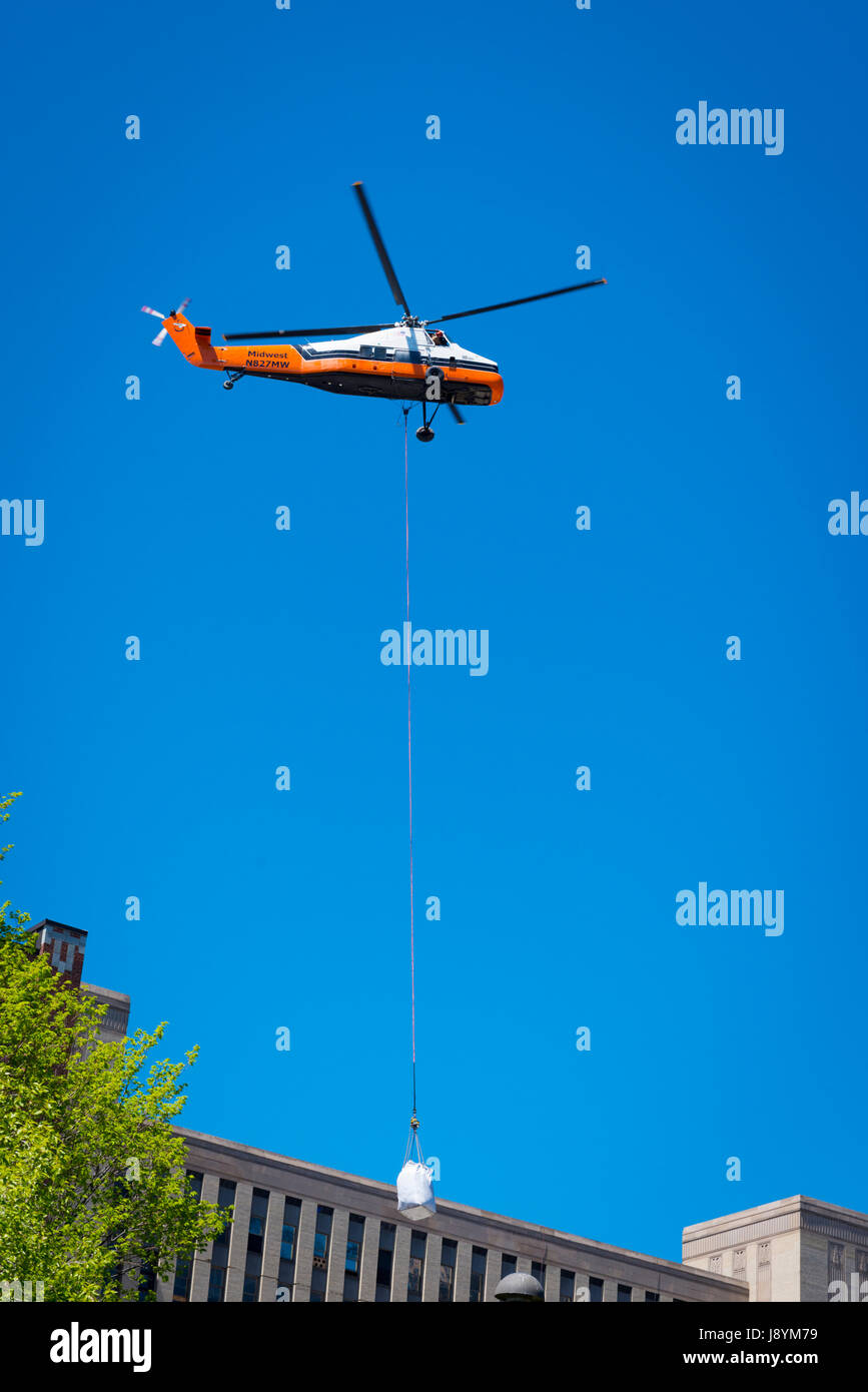 View Chicago River Illinois Midwest Helicopter lifting builders rubble from top of high-rise to ground for collection - Stock Image