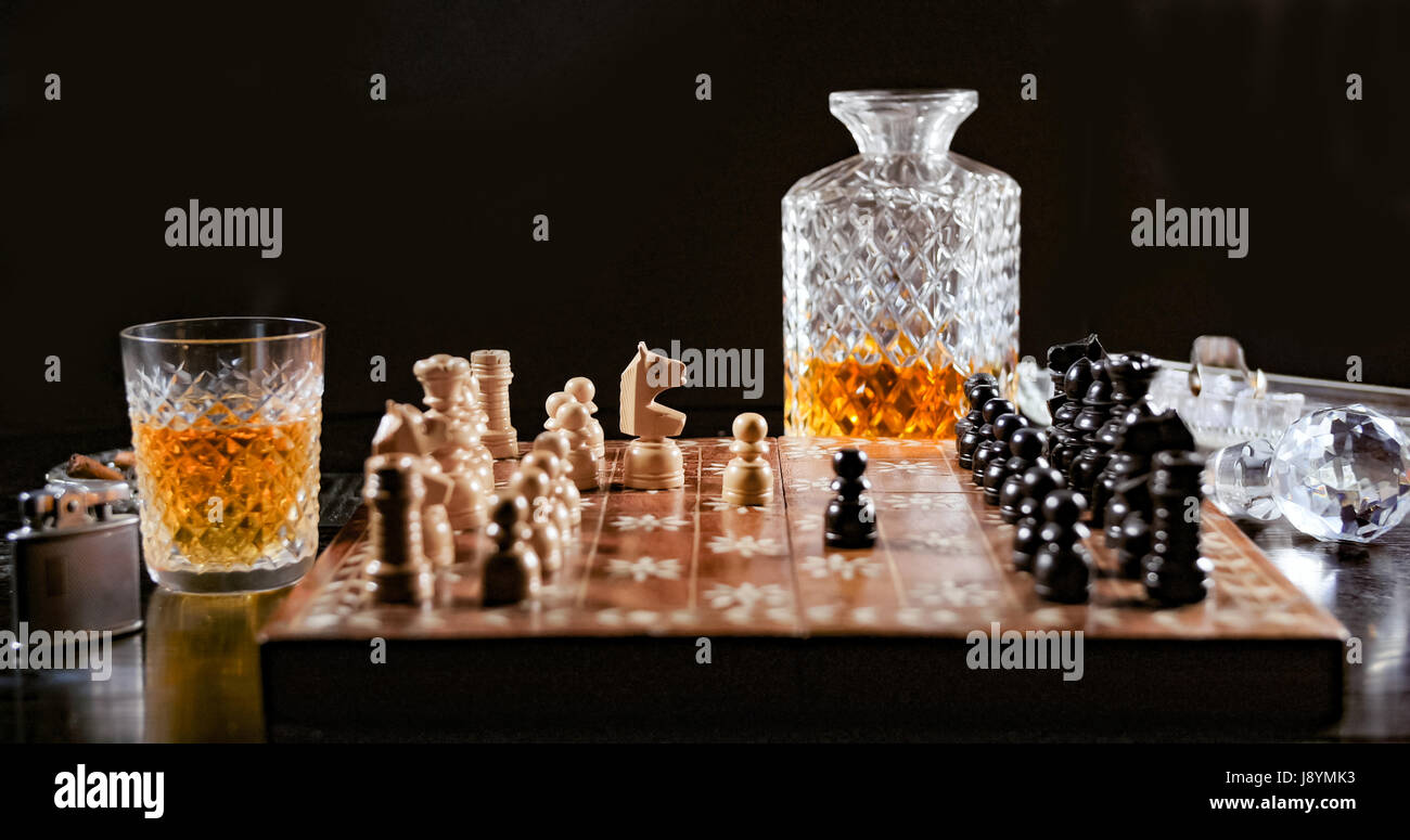 Playing a game of chess with a glass of whiskey and a cigar - Stock Image