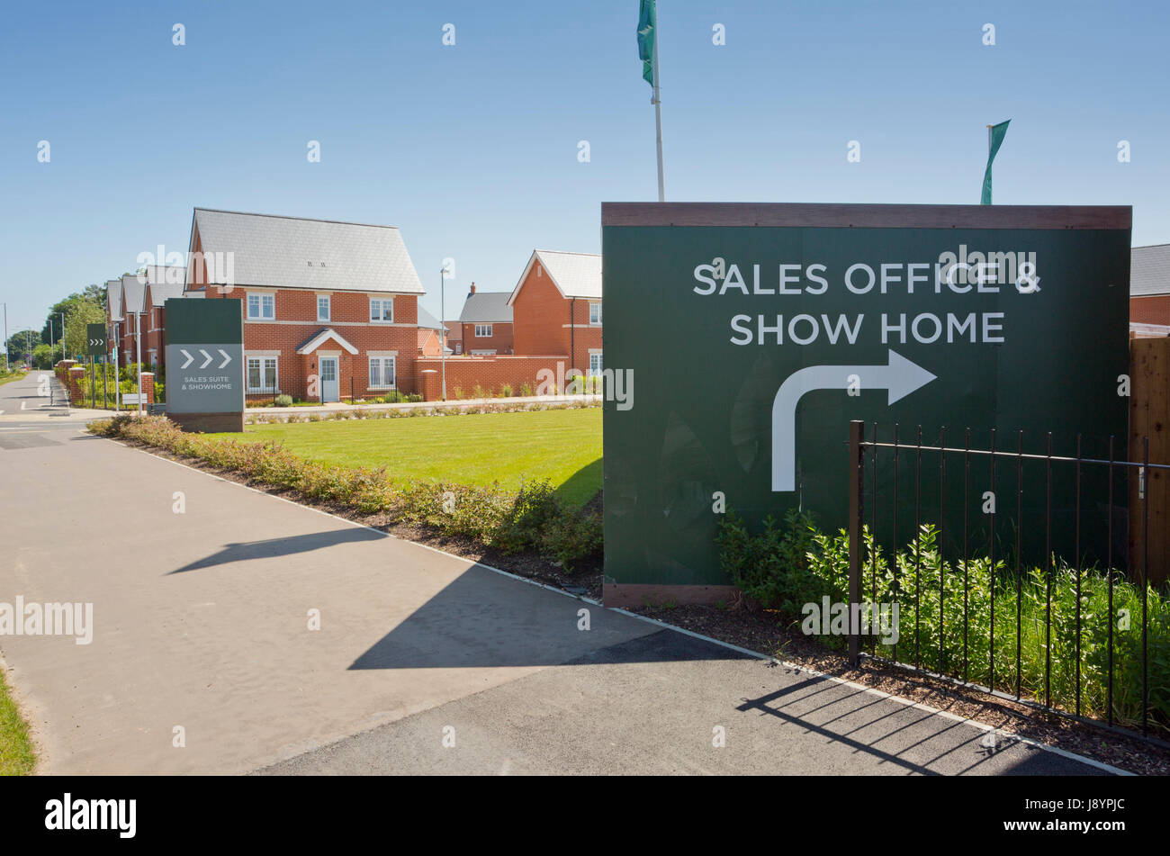 An empty street in a mostly complete new housing development, with show home and sales - Stock Image