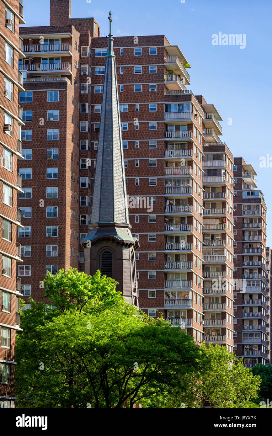 The spire of Church of The Holy Apostles contrasting with the building terraces of Penn South in Chelsea in summer. - Stock Image