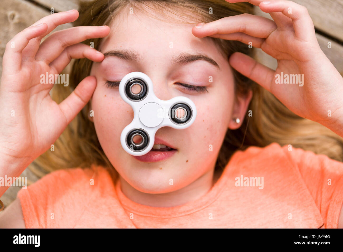 Female teenager playing with fidget spinner spinning toy on her nose  Model Release: Yes.  Property release: No. - Stock Image