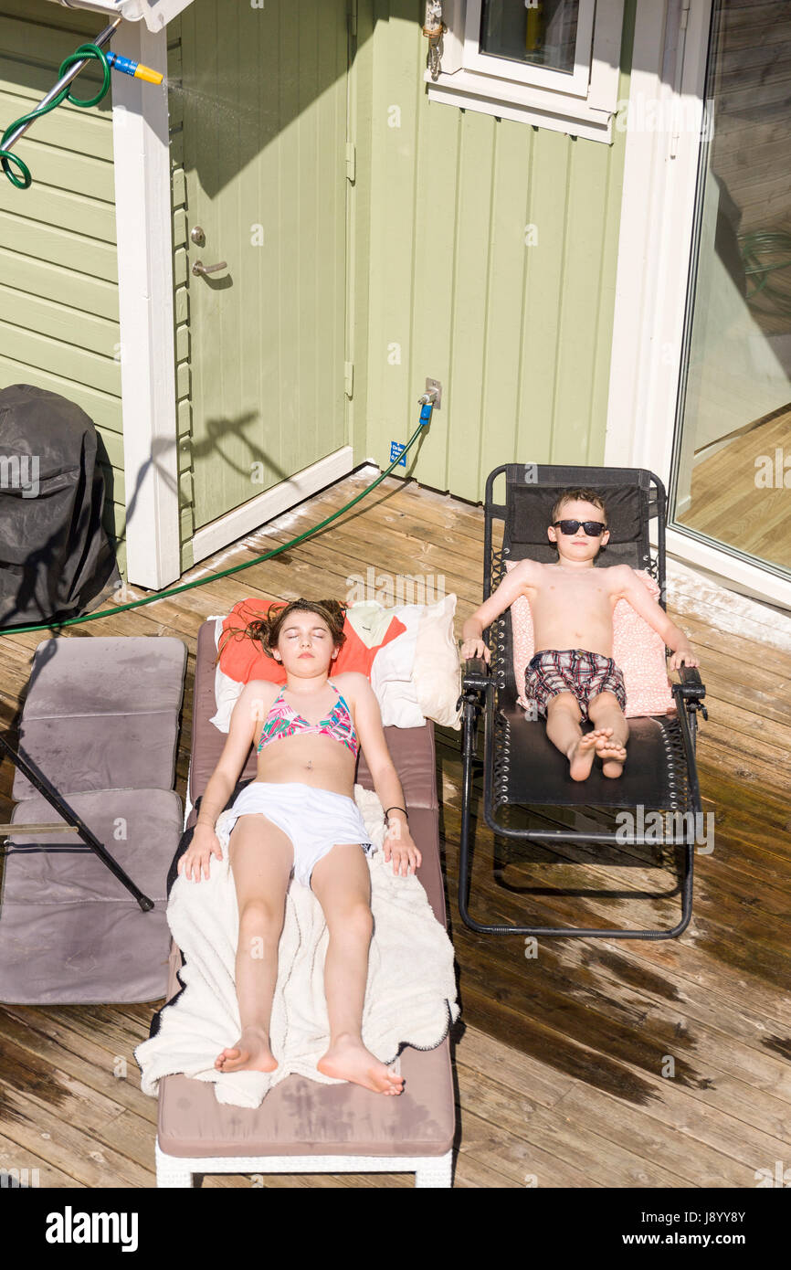Female teenager and young boy tanning on sun loungers outdoors with water sprinkler sprinkling from above  Model - Stock Image