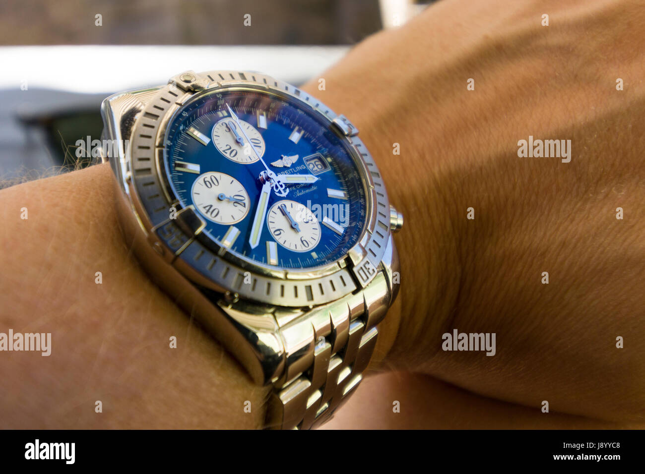 Luxury Breitling Chronomat Evolution watch with blue face on man's wrist  Model Release: Yes.  Property release: - Stock Image