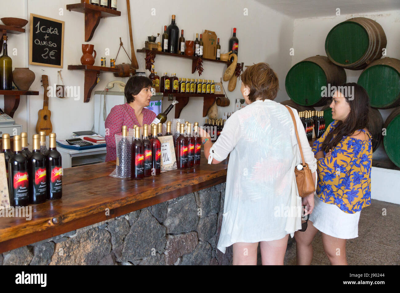 Lanzarote wine - two tourists wine tasting in a Lanzarote vineyard or bodega, Lanzarote, Canary Islands, Europe - Stock Image