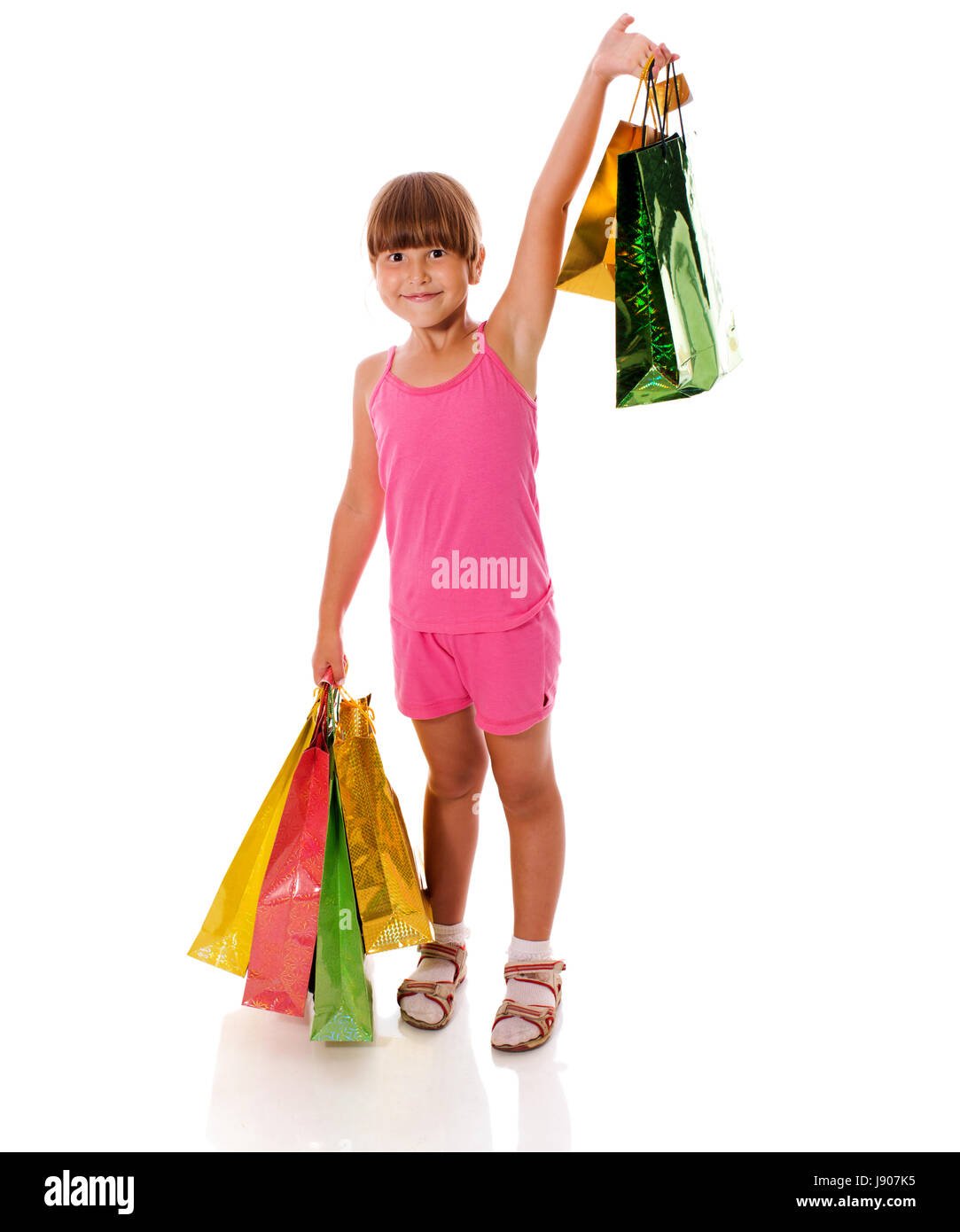 Smiling six years Girl holding presents bags isolated - Stock Image