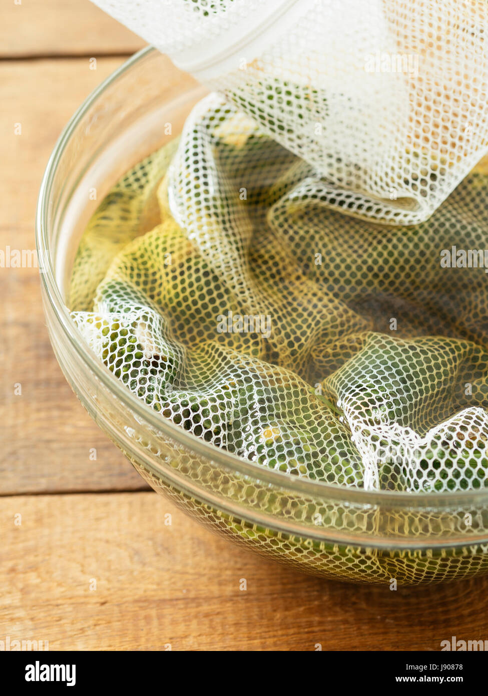 Shopped comfrey leaves in a wash net soaking in hot water to make comfrey tea. - Stock Image