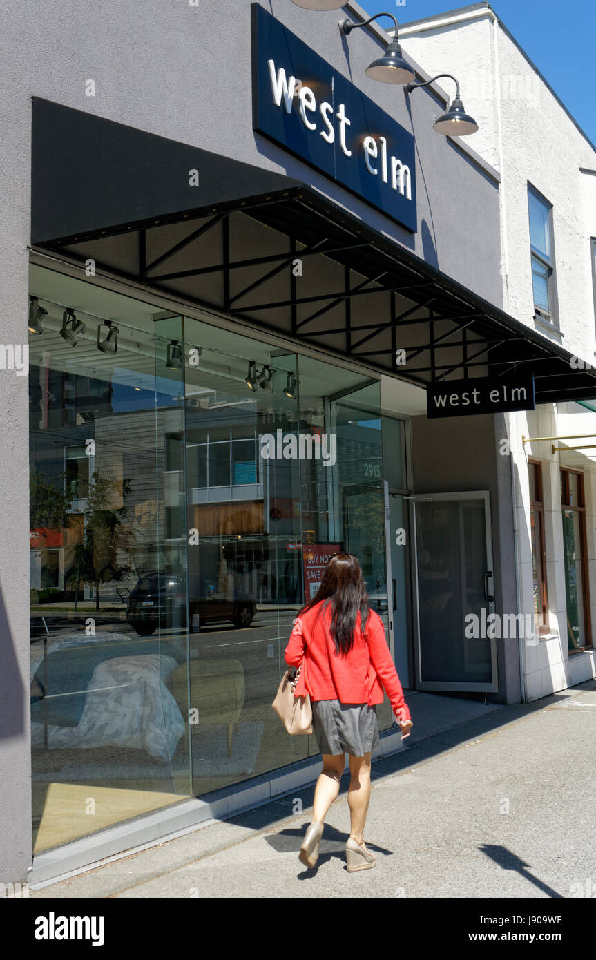 Young woman walking past a West Elm home decor store on south Granville Street shopping district in Vancouver, British - Stock Image