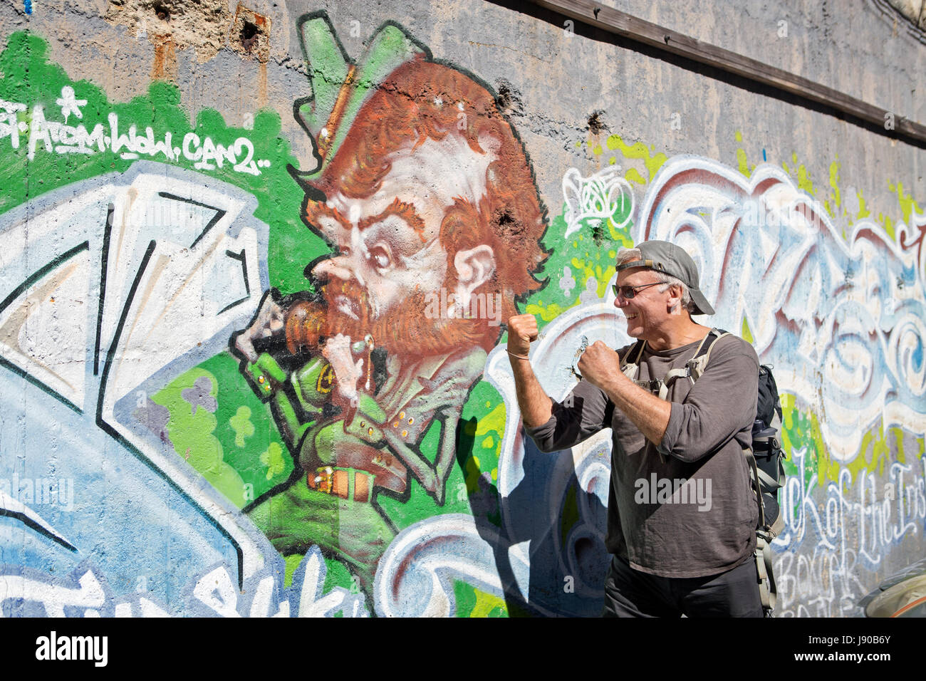 Irish Man with fists up next to Irish caricature graffiti on the wall in Wellington New Zealand - Stock Image