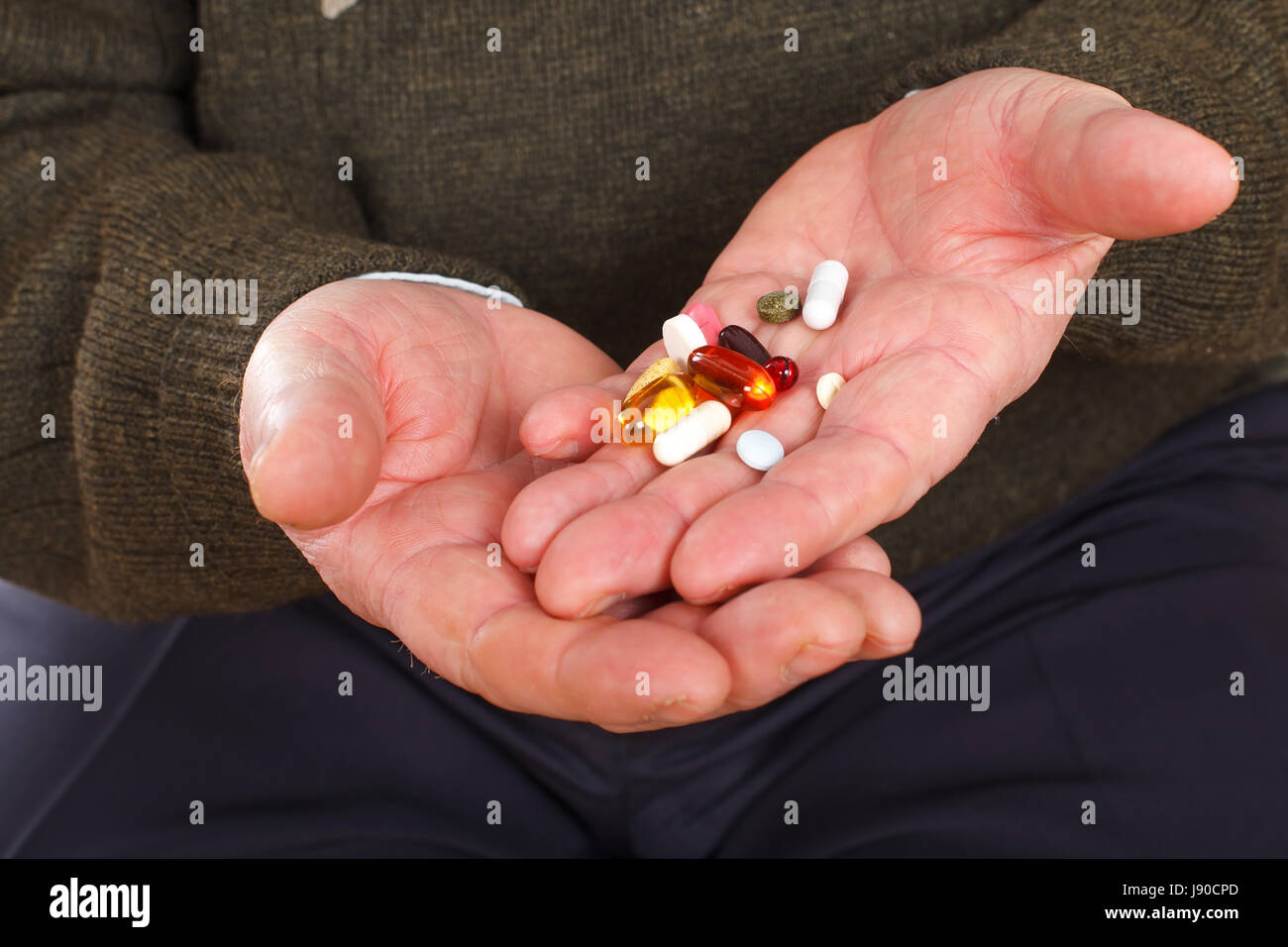 Close up picture on an elderly man holding his pills - Stock Image