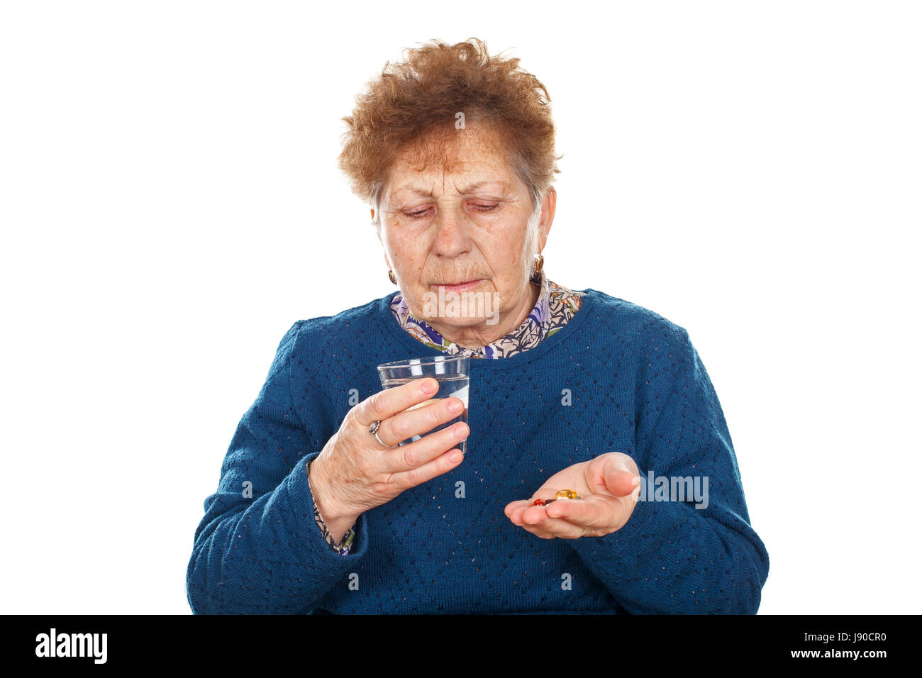 Portrait of a sick elderly woman taking her pills - Stock Image