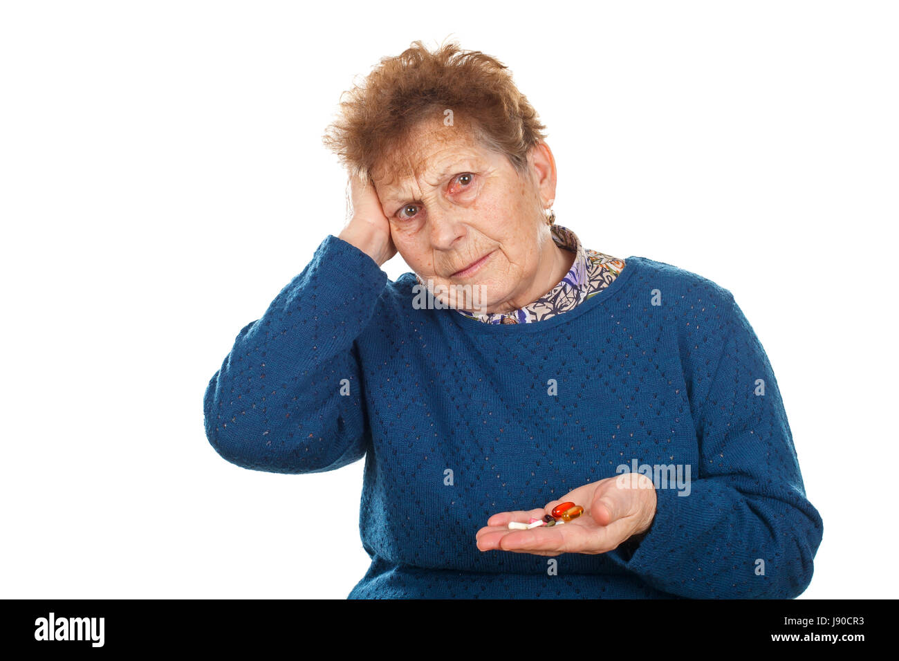 Close up photo of a senior woman's hands, holding her pills - Stock Image