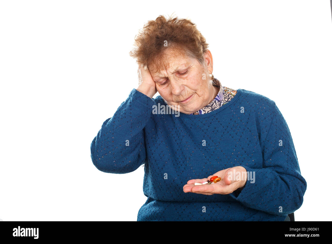 Picture of a senior woman having a headache, holding her pills - Stock Image