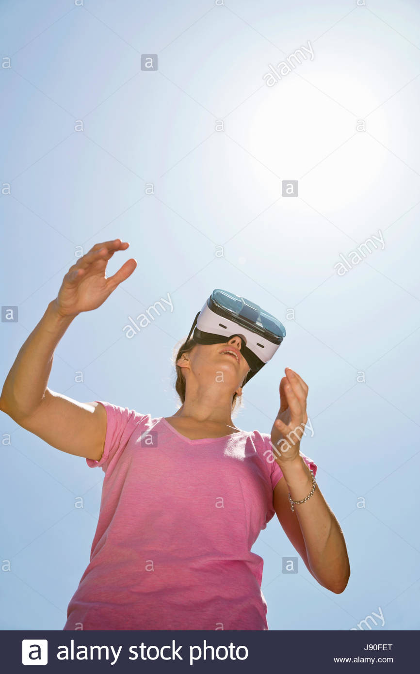 Low Angle View Of Woman Outdoors Wearing Virtual Reality Headset - Stock Image