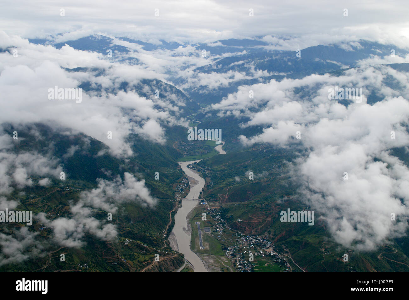 Mountains of Nepal. Beautiful helicopter view of a river valley between cloudy mountains. - Stock Image
