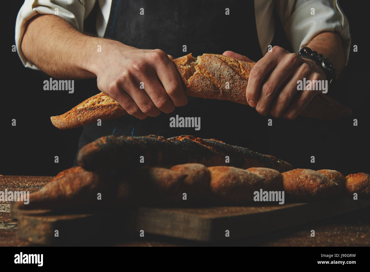 Baker's hands break the baguette Stock Photo
