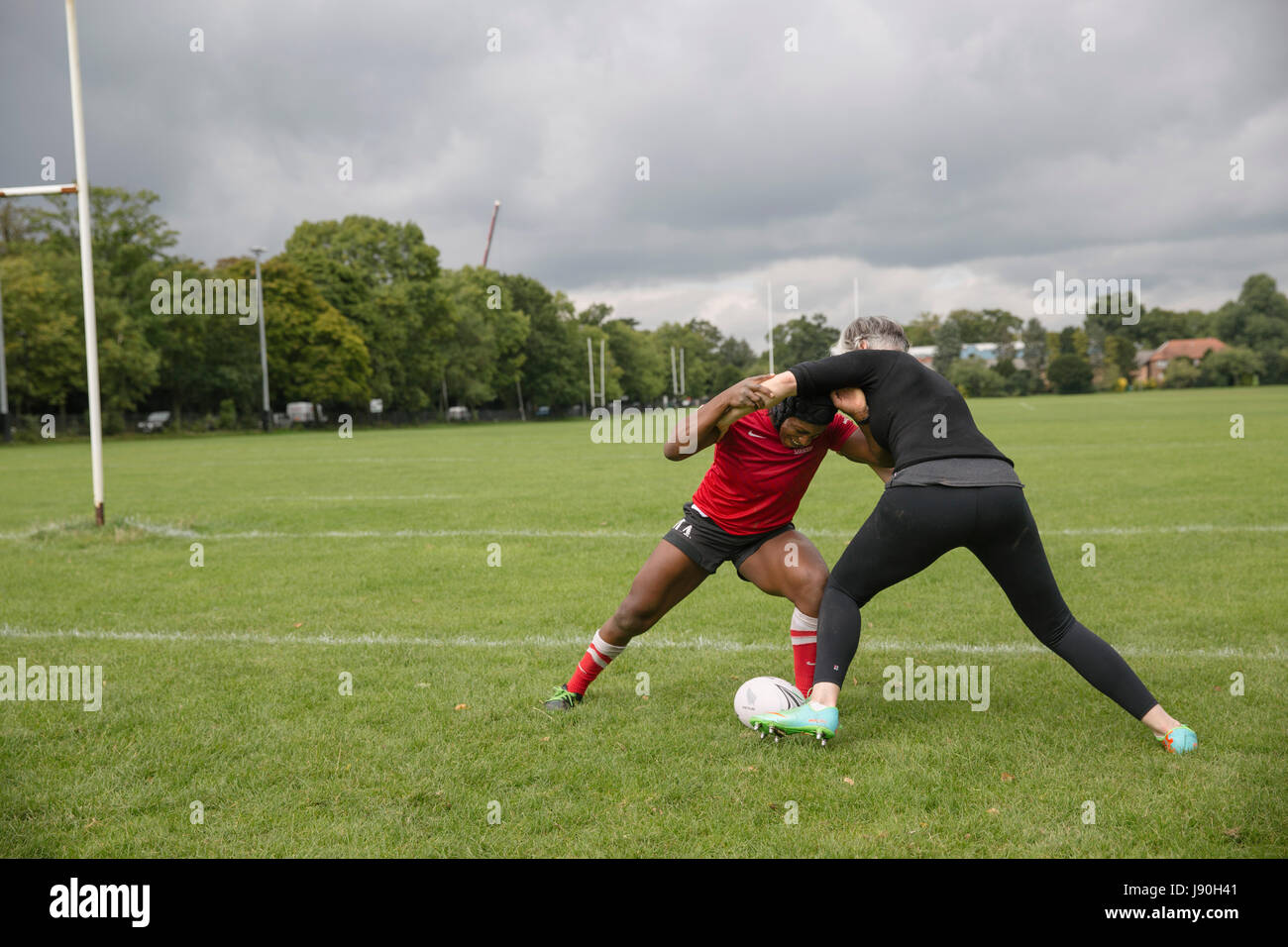 Maggie Alphonsi MBE, teaches Lucy Killgren the basics of rugby tackling. - Stock Image