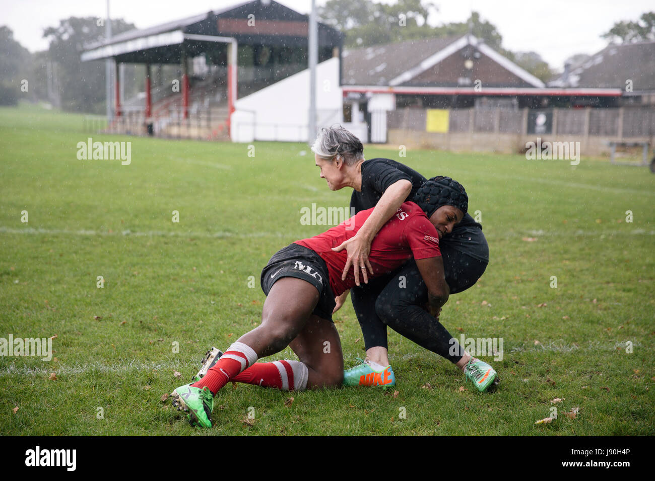 Ex-England rugby player Maggie Alphonsi tackles Lucy Killgren to the ground at the Saracens training ground. - Stock Image