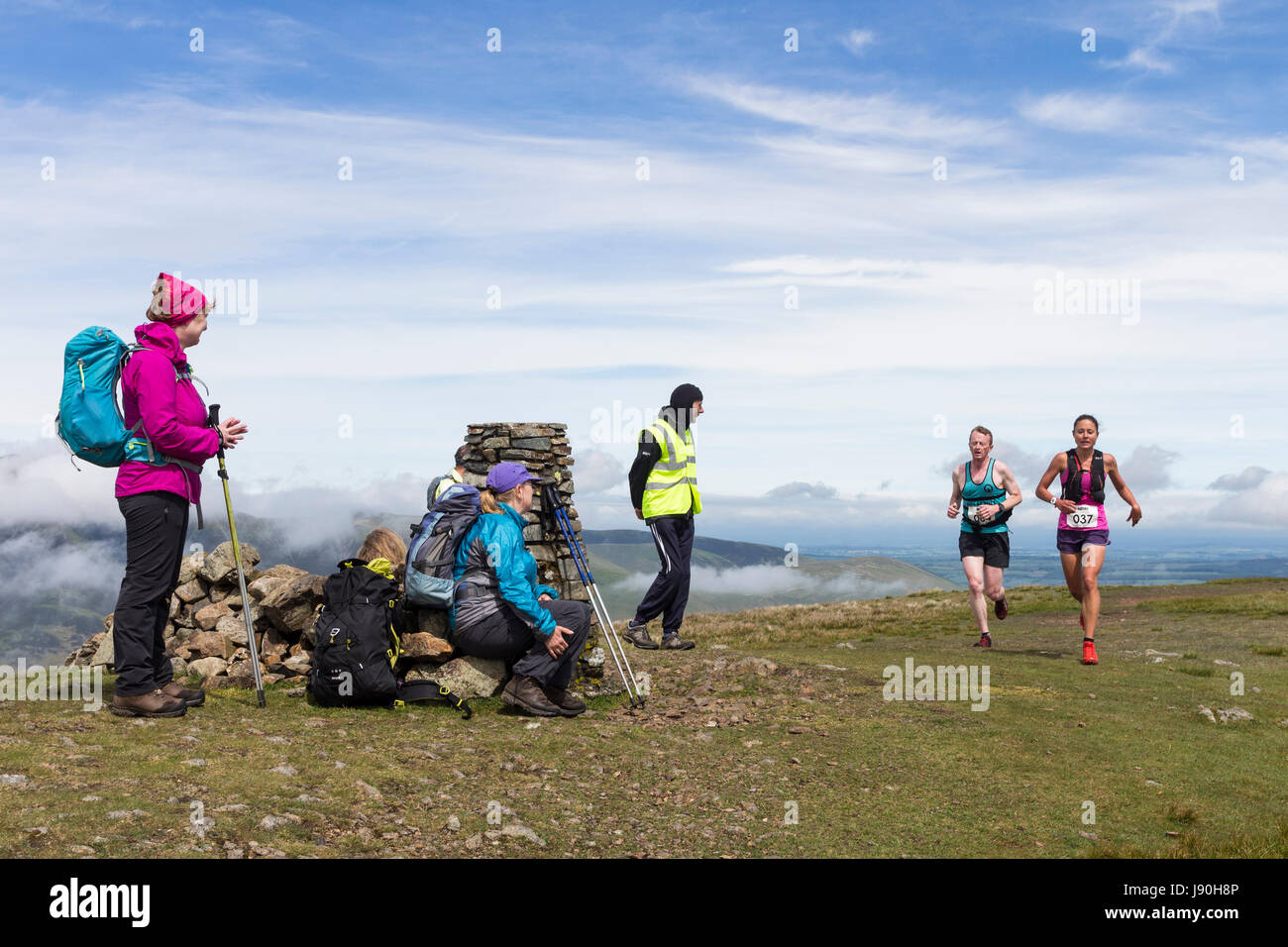 Walkers on the Summit of Clough Head Watching Runners Taking Part in the Helvellyn and the Dodds Fell Race, Lake - Stock Image