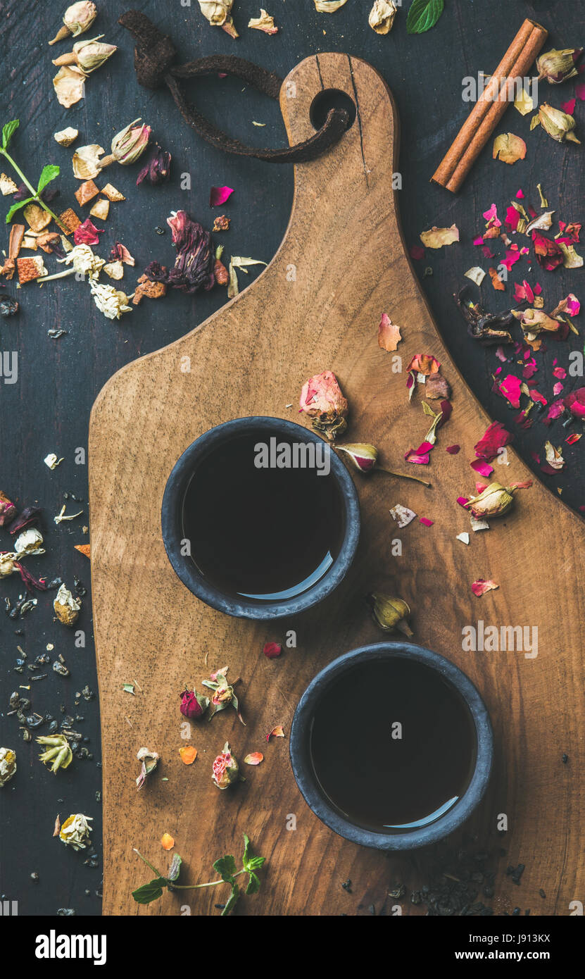 Chinese black tea in black stoneware cups with herbs, flowers - Stock Image