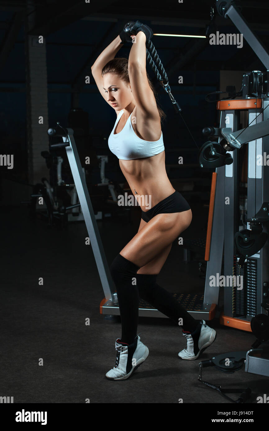 Woman lifting weights on a machine for bodybuilders. She has a beautiful body with big muscles. - Stock Image