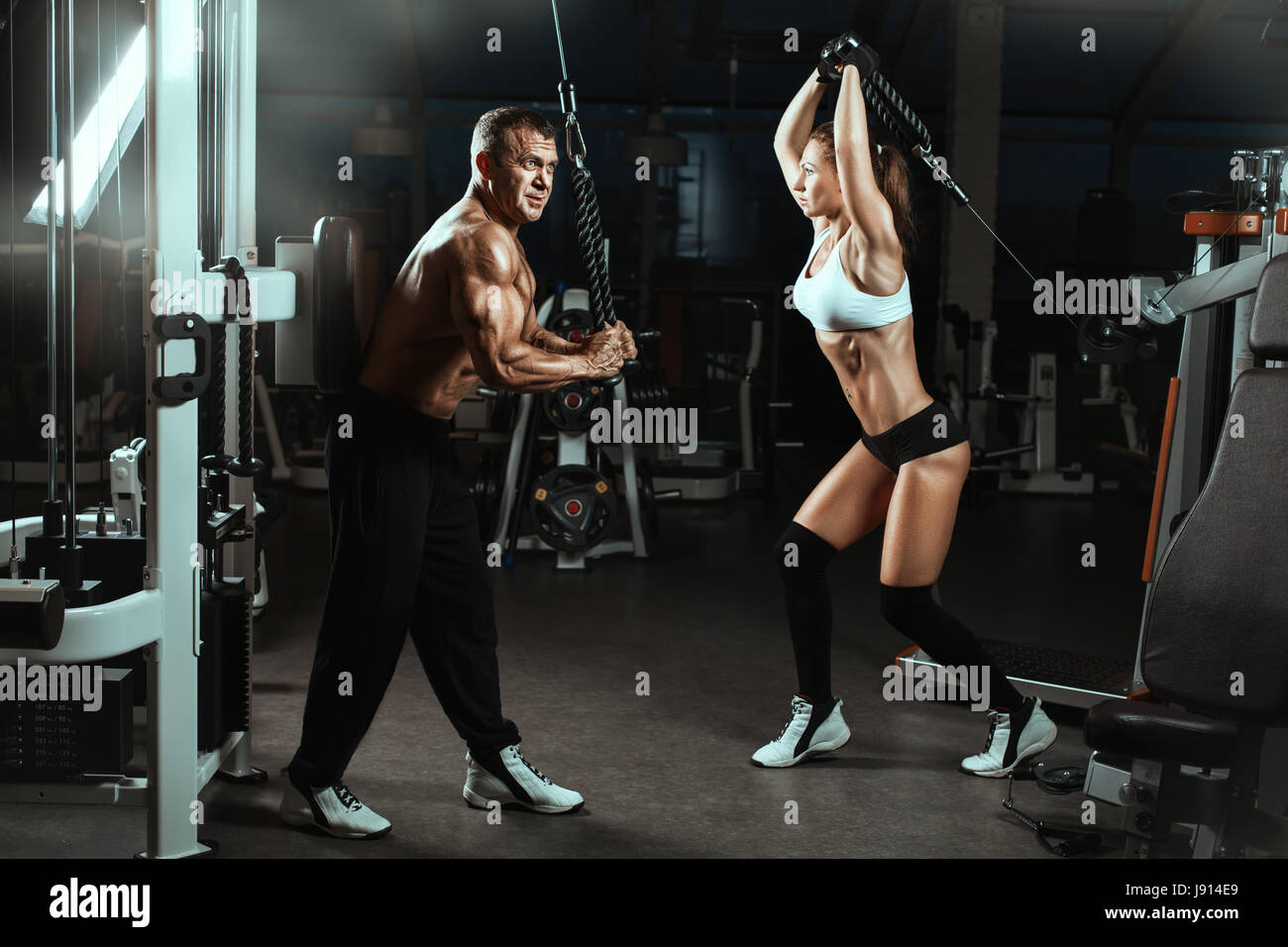 Man and a woman trained muscles in the gym.  They train with machines for bodybuilders. - Stock Image