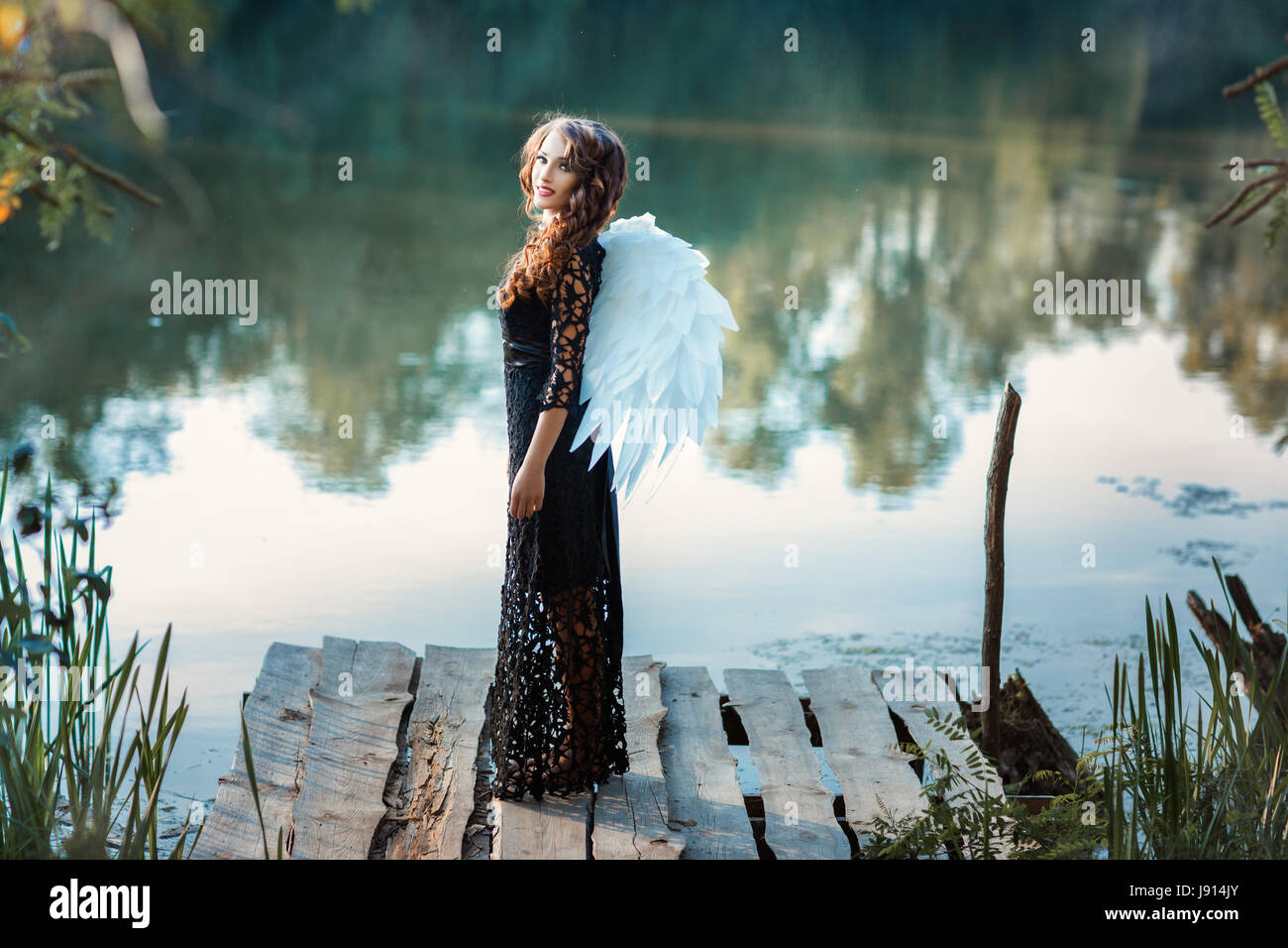 Girl with angel wings standing on the pier and smiling. This occurs in the open air on a river. - Stock Image