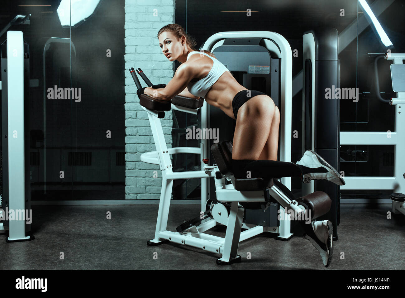Woman on the machine for bodybuilders doing exercise. She shakes her legs. - Stock Image