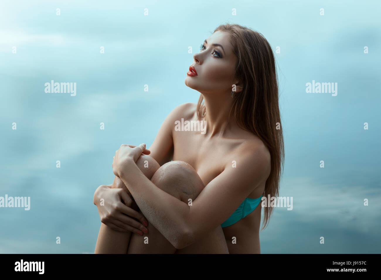 Portrait of a beautiful and tender girl in the clouds. She pursed her knees and wrapped her arms. - Stock Image