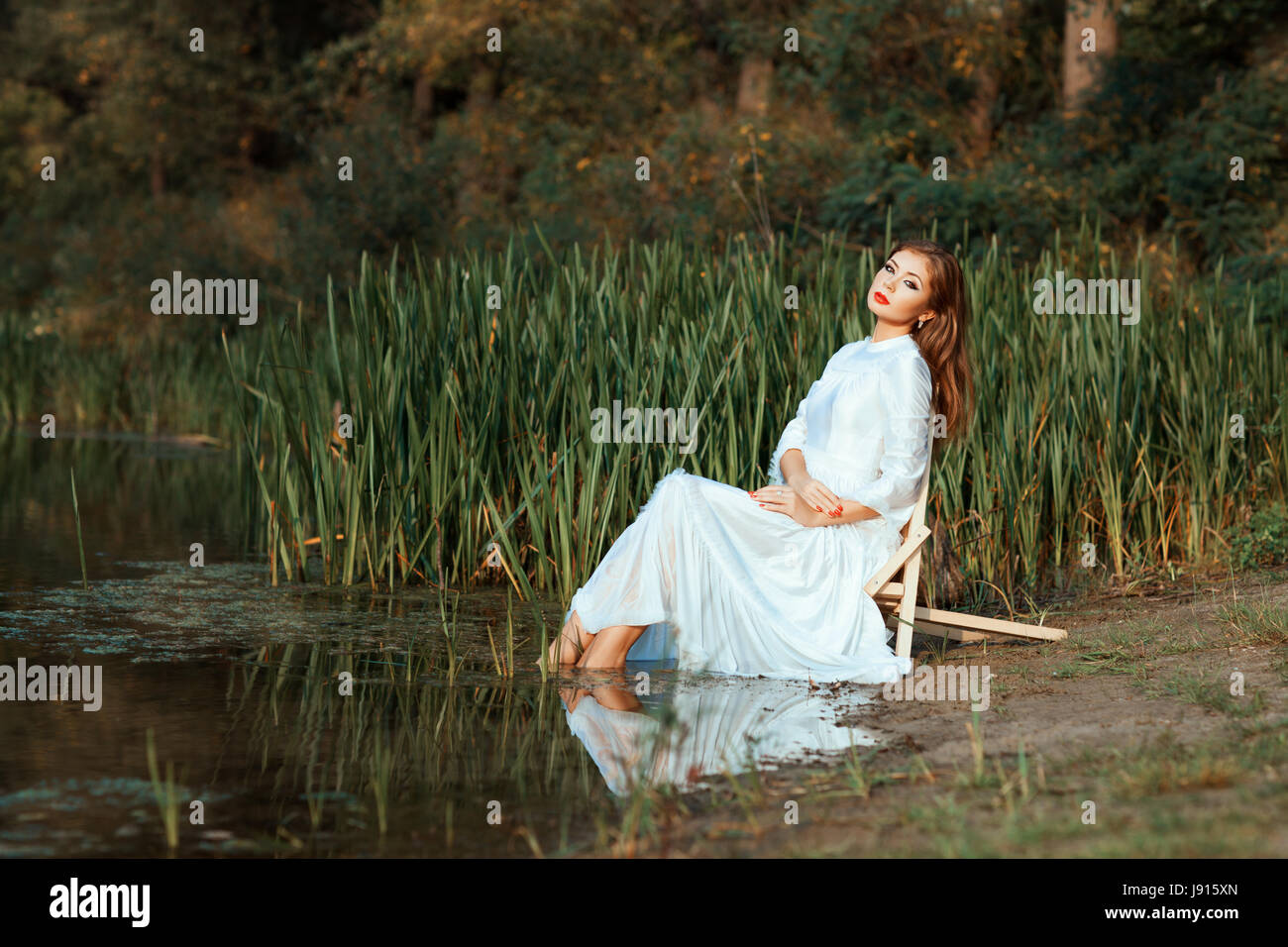 Girl in a white dress sitting dipping feet in the lake. This a summer day. - Stock Image