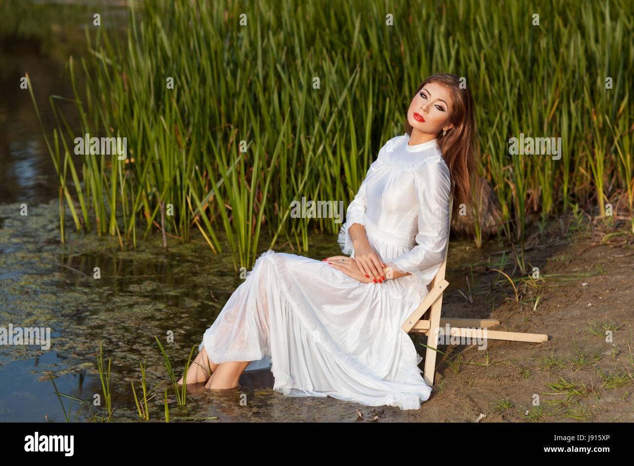 Beautiful girl sits on the shore of the lake. Her legs in the water. - Stock Image