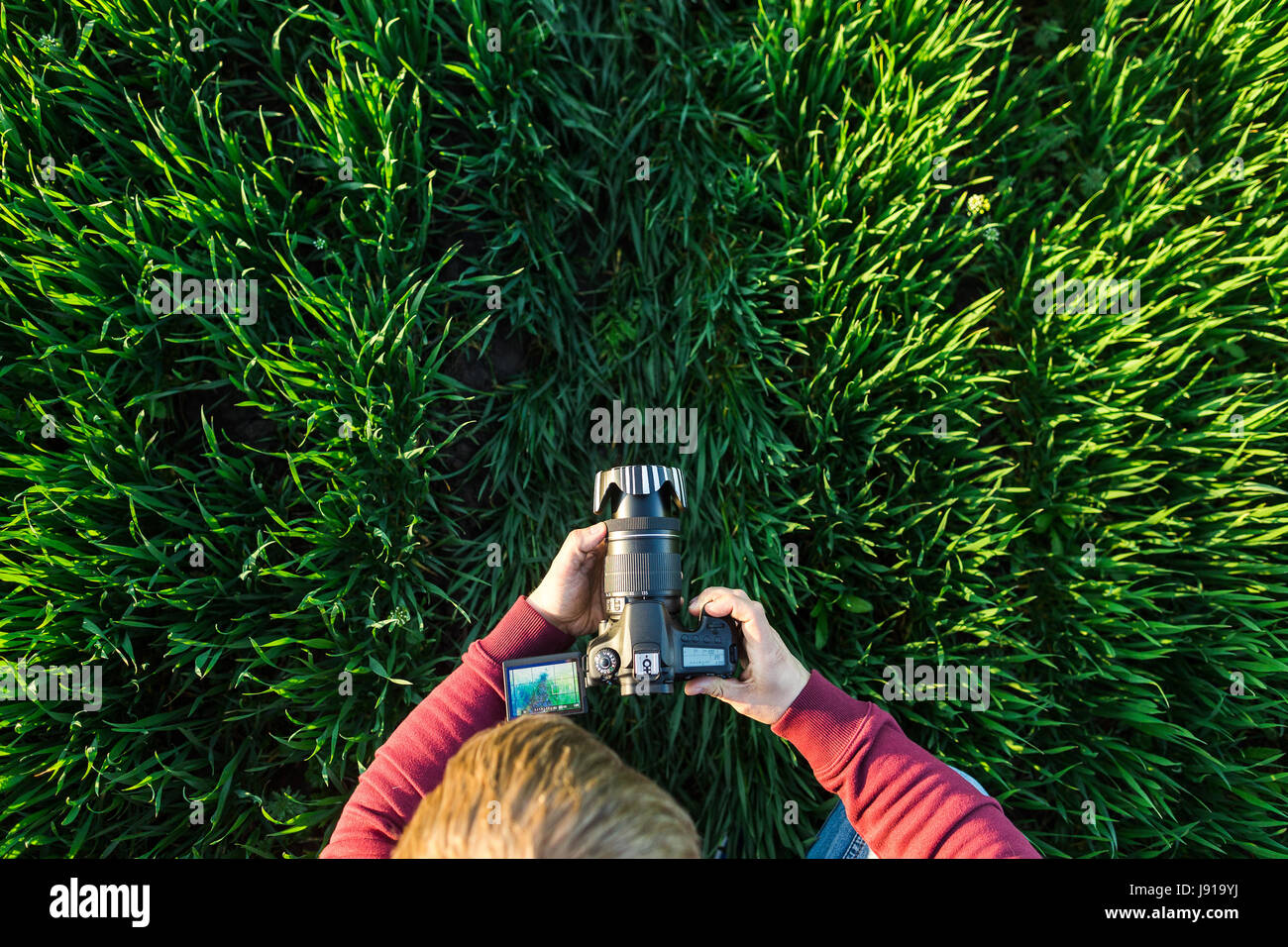fascinating photography and process of shooting concept - male man takes photos on a digital camera with LCD display - Stock Image