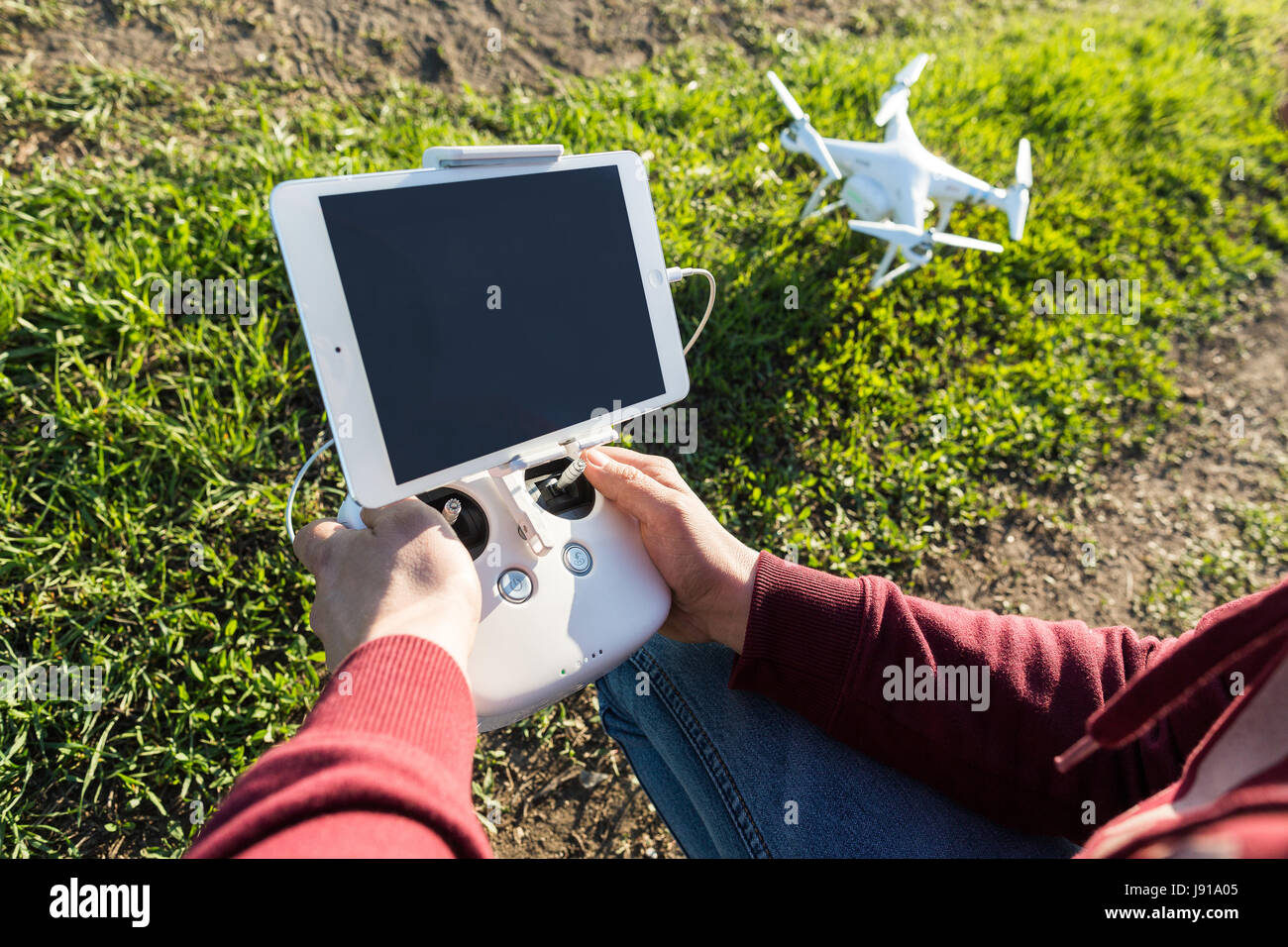 quadcopter flights outdoors, aerial imagery and tech hobby concept - hands of pilot with remote control, tablet - Stock Image