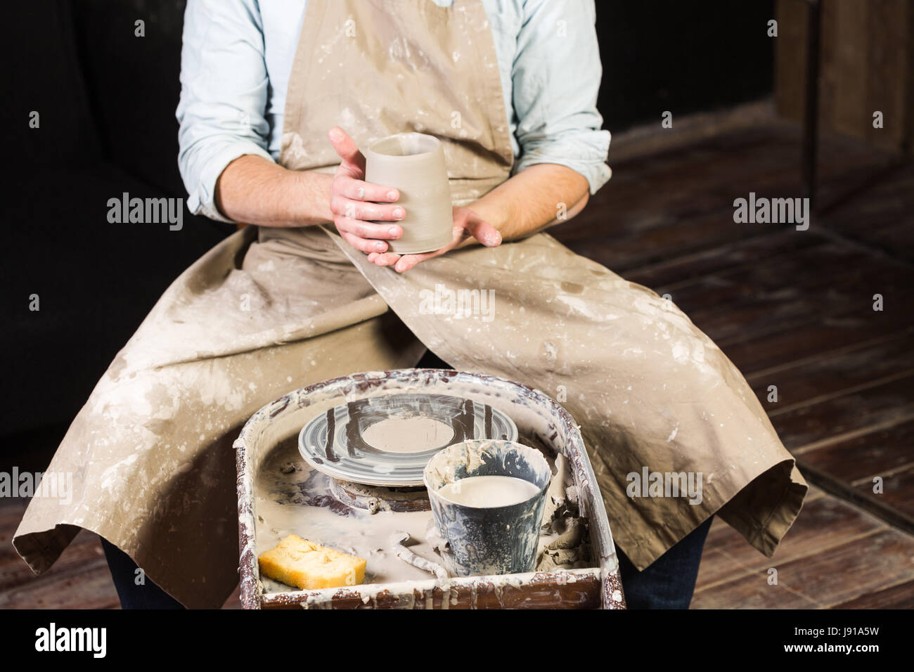 pottery, workshop, ceramics art concept - close-up on male hands holding unfired clay cup, a man examines a fresh - Stock Image