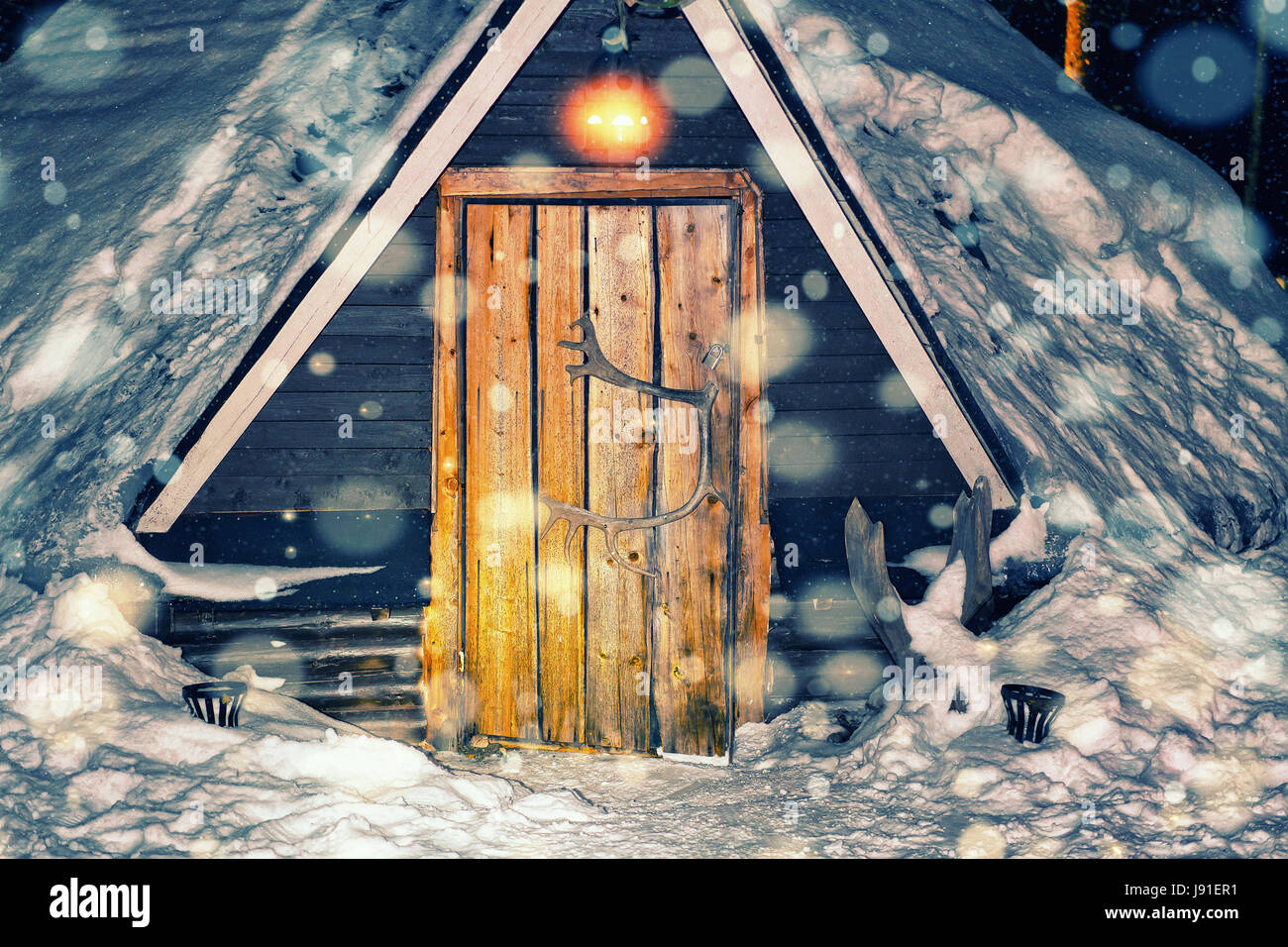 Lappish traditional house at the reindeer farm in winter Rovaniemi, Lapland, Finland. Night snowfall. Toned - Stock Image