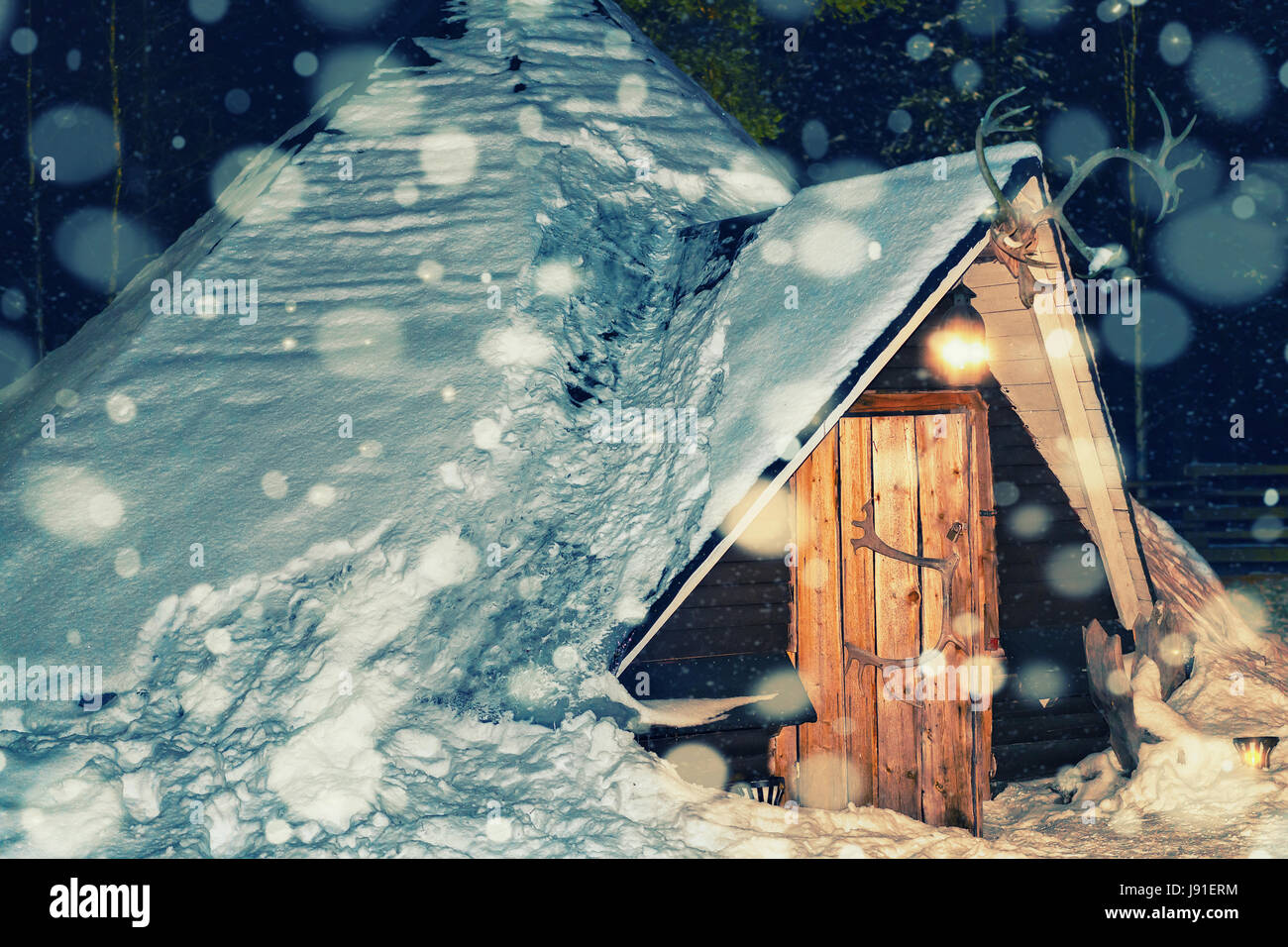 Lappish traditional house of the reindeer farm in winter Rovaniemi, Lapland, Finland. Night snowfall. Toned - Stock Image