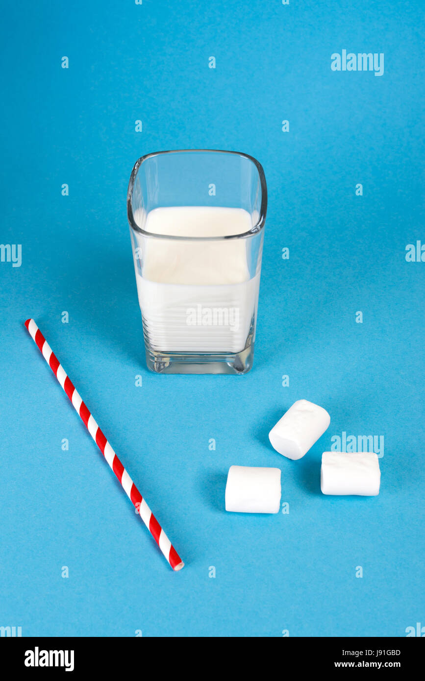 Glass of milk with retro cocktail tube on blue background with sweet marshmallows. - Stock Image