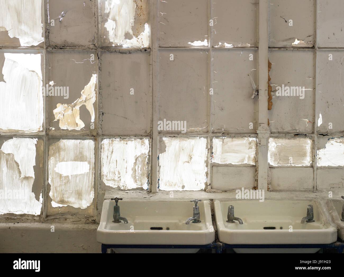 dirty white bathroom sinks in toilet block - Stock Image
