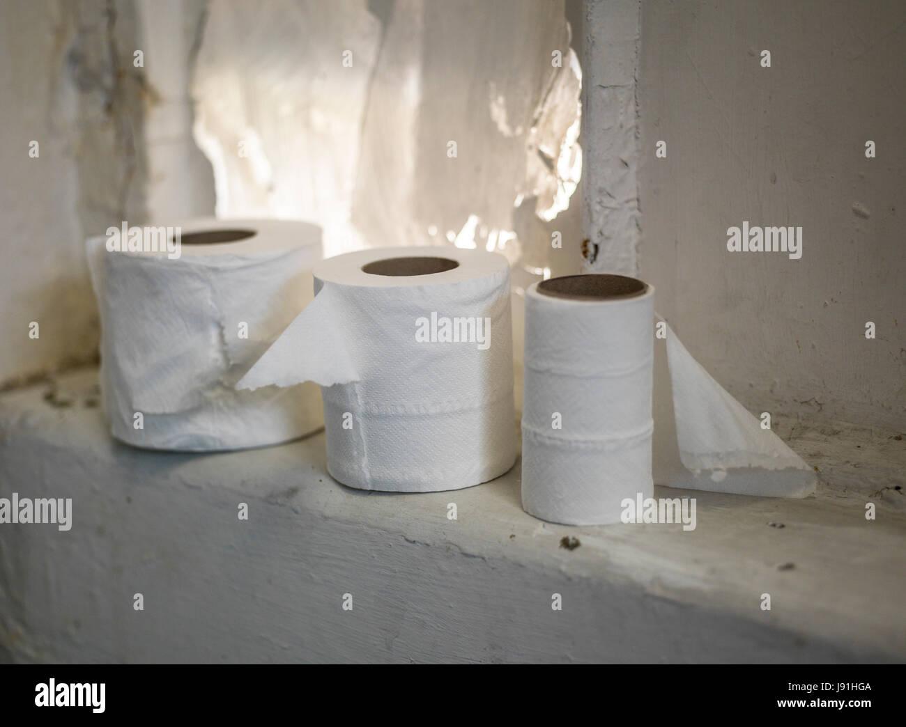 toilet rolls in messy bathroom - Stock Image
