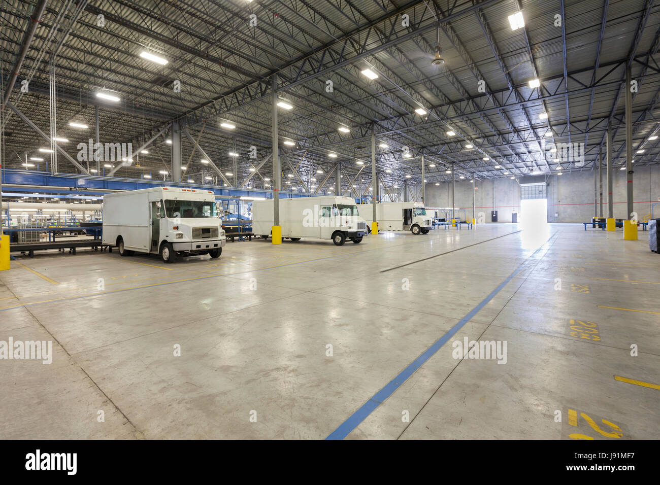 Delivery trucks inside distribution warehouse. - Stock Image