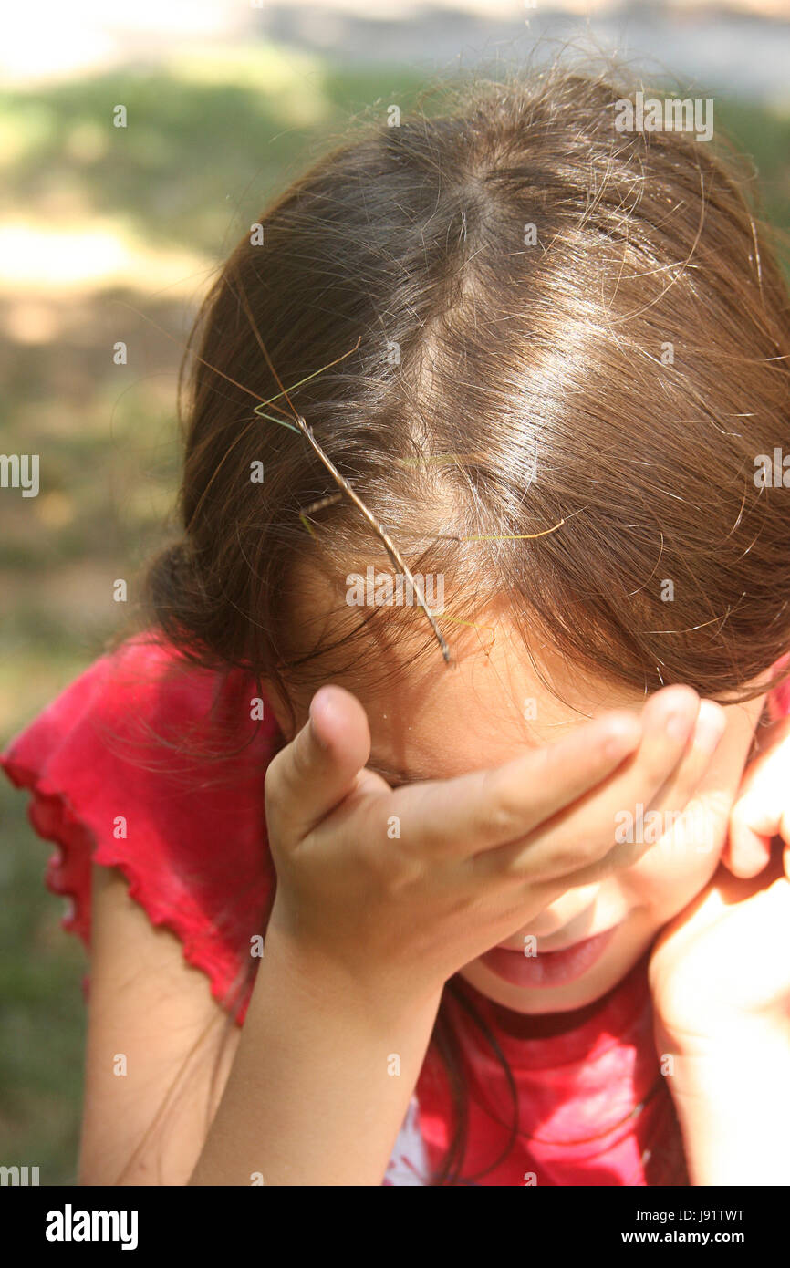 Little girl with walking stick insect climbing on her head - Stock Image
